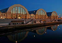 Riga central market in dusk time with pavillions reflecting in canal water