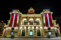 Latvia National theatre illuminated at night with Latvia flags